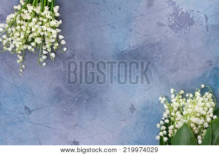 Lilly of the valley flowers for Mothers Day on gray stone background with copy space