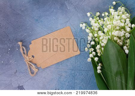 Lilly of the valley flowers on for Mothers Day on gray stone background with copy space on paper note