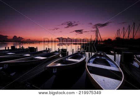 Small motorboats docked at a platform in a calm lake under a purple and orange dawn