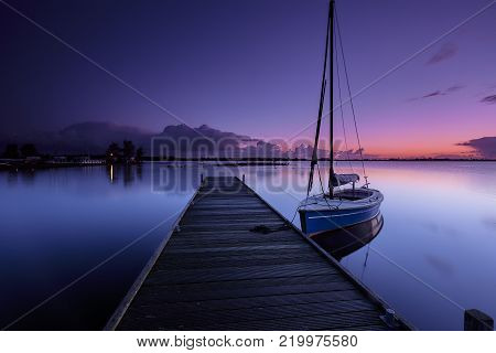 Sailboat at a wooden platform in early morning in a calm lake under a red and blue sunrise