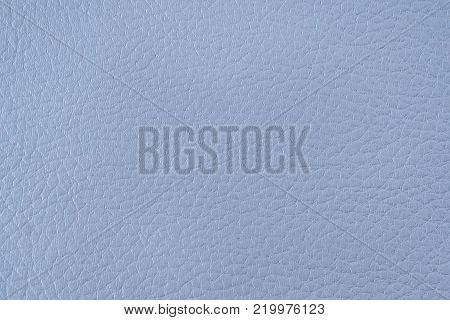 Texture of artificial leather. Light blue background or leatherette backdrop. Fine embossing.