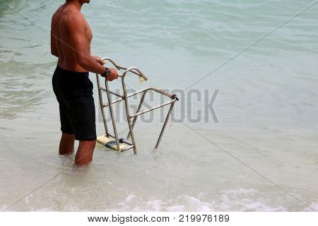 Asian strongest man, Lifeguards with ladders for long-tail boat on the beach.