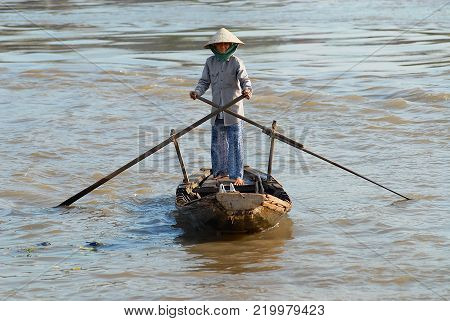 CAI BE, VIETNAM - FEBRUARY 16, 2007: Unidentified senior woman crosses Mekong river by a traditional wooden paddleboat in Cai Be, Vietnam. Cai Be is often called the