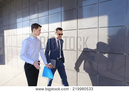 Two attractive confident young businessman male guys go and discuss important issues, hurry to a meeting, make decisions, solve problems, share business ideas, smiling, holding colored folders in hands, go along gray walls of modern business center outdoo