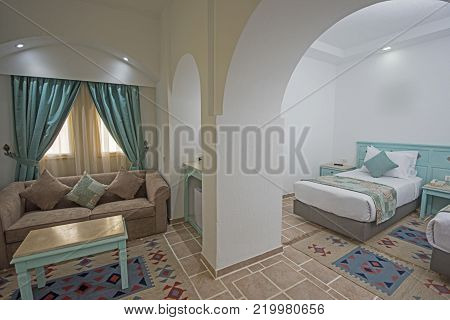 Bed in suite of a luxury hotel room with curtains and lounge area