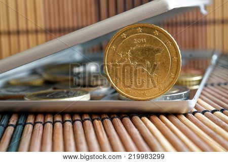 Pile of Euro coins in mirror reflect wallet lies on wooden bamboo table background Denomination is 50 euro cents - back side