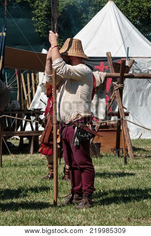 Guard with Pole Weapon and Straw Hat during Medieval Event Fair near White Tent.