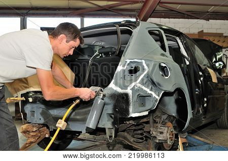 Car mechanic at work in body shop.
