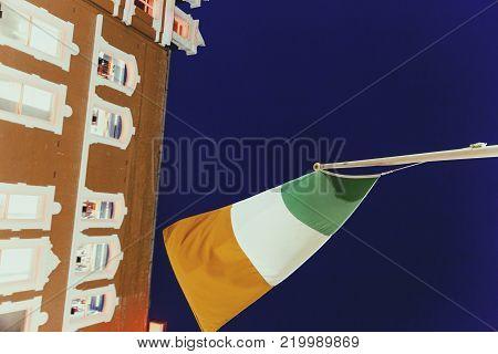 DUBLIN, IRELAND - December 24th, 2017: Irish flag waving in front of Grafton Street