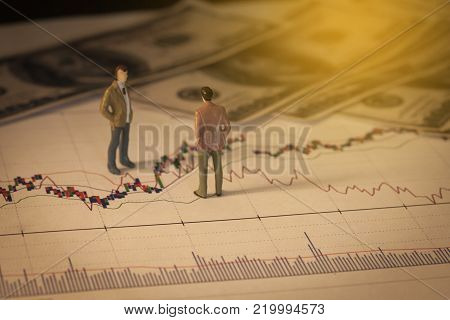 Miniature Business Man On Stock Market Graph Or Chart,image For Business Concept.