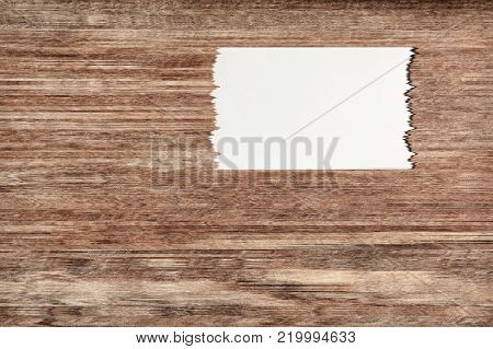 White torn off paper sheet on brown wooden wall with empty space for text.Digitally altered image.