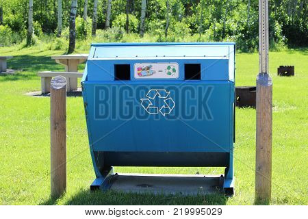 A recycle container in a green park.
