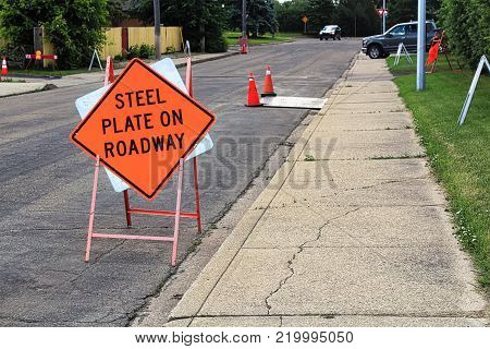 Orange steel plate on roadway construction sign.
