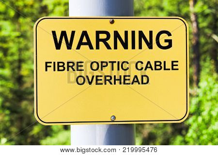 A warning fibre optic cable overhead sign.