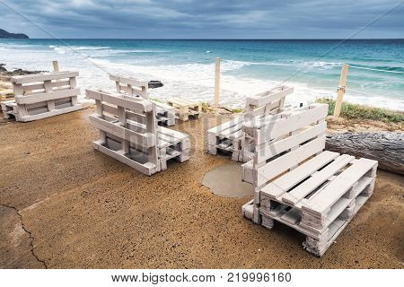 Standard white wooden furniture made of cargo pallets, cheap seaside bar terrace. Porto Santo island, Madeira archipelago, Portugal