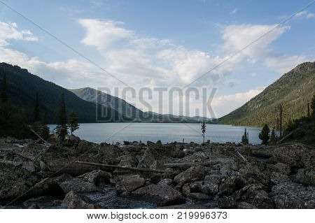 Rocks near Multinskoe lake, Altai mountains. Russia. The beautiful mountain scenery. The lake in the foreground with mountains in the background on top of which the snow