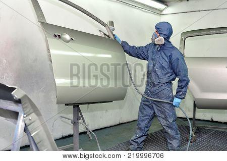 Car body worker painting silver car door.