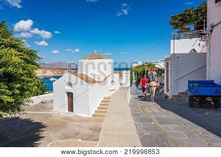 Girl riding donkey on her way to Acropolis of Lindos, Greek orthodox church (Rhodes, Greece)
