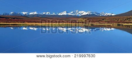 Scenic Mountain Range reflecting in small Lake, with tundra in autum colors, Dempster Highway, Yukon Territory, Canada