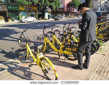 ZHONGSHAN;GUANGDONG;China-December 1;2017:office gentleman prepaing to ride a shared bike.Bicycle-sharing is very popular in China.