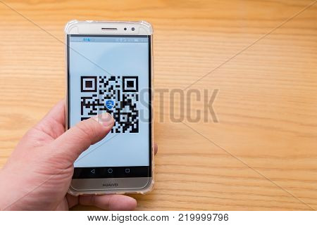 Zhongshan,China-December 26, 2017:Chinese man checking the Alipay QR code on the mobile.QR code for payment and money transfering becomes very common and popular in China,fast and safe.