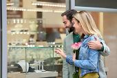 Young happy couple near showcase of jewelry store poster