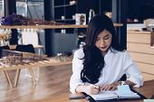 asian businesswoman write note on notebook at workplace. startup woman working with business plan report document at office.  young female entrepreneur analyze accounting market data.  financial adviser with paperwork on table. poster