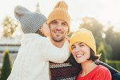 Sincere emotions. Little cute girl in knitted hat and white warm sweater kisses her father with love. Friendly affectionate couple pose together outdoors smile happily have wonderful relationships poster