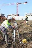 Civil engineers on site with surveying equipment poster