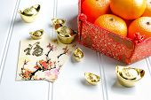 Chinese New yearred envelope packet (ang pow) and red felt fabric bag with gold ingots and oranges and flower on white wood table topChinese Language mean Happiness and on ingot mean wealthy poster