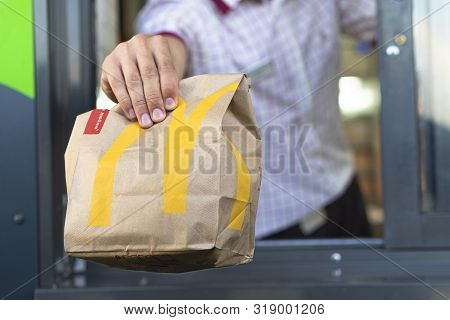 Sankt-petersburg/russia - July 21 2019: Mcdonalds Worker Holding Bag Of Fast Food. Hand With A Paper