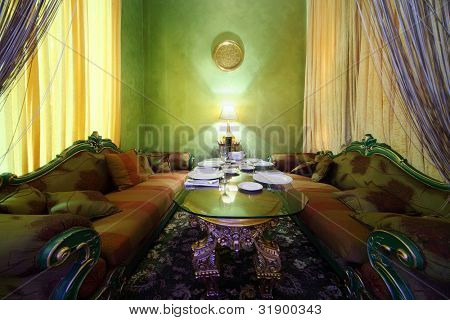 glass table with serving, lamp and carved sofas in eastern luxury restaurant