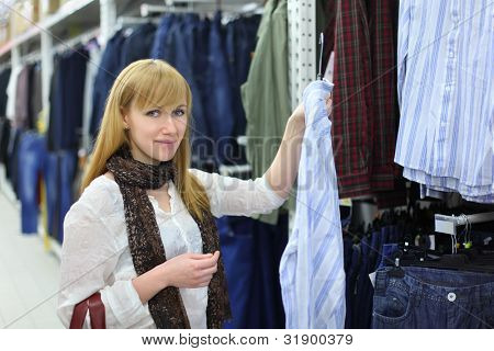 Blonde girl wearing white shirt chooses male shirt in large shop; shallow depth of field