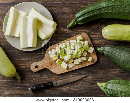 Zucchini Harvest. Slices Farm Organic Zucchini Cubes For Freezing On Woodencutting Board Over Brown
