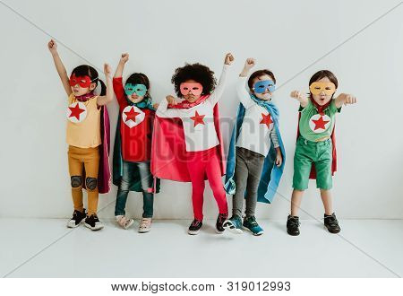 Group Of Diverse Children Playing Superhero On The White Wall Background. Superhero Concept. Happy T