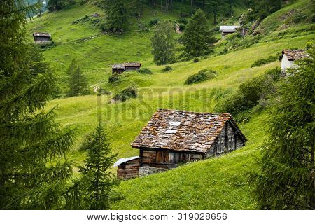 Amazing View In The Mountains With Old Wooden Barns Among The Meadow, Zermatt Valley In Switzerland.
