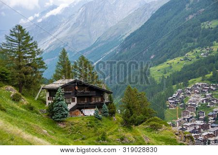 Spectacular Summer Alpine Landscape, Mountain Swiss Wooden Chalet With High Mountains In Background,