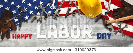 US American flag with work tools on worn white wooden background. For USA Labor day celebration. With Happy Labor Day text.