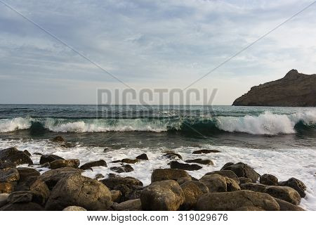 Cold Black Sea In Early Spring. The Waves Are Beating On The Big Stones On The Shore Of The Robber B