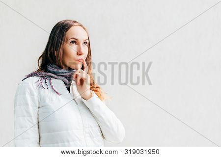 Caucasian Girl Looks Away Thoughtfully With Slight Smirk Putting Finger To The Corner Of Her Mouth O