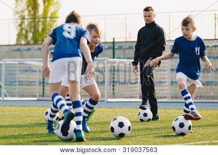 Soccer Camp For Kids. Boys Practice Football Dribbling In A Field. Players Develop Soccer Dribbling