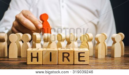 Wooden Blocks With The Word Hire. Headhunter Selects A Person From The Crowd. Human Resource Managem