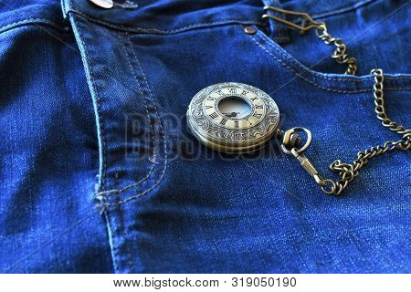 A Close Up Image Of An Antique Pocket Watch And Old Blue Jeans.