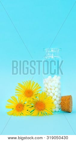 Classical Homeopathy Globules In Vintage Glass Bottles And Flowers On Blue Background. Alternative H