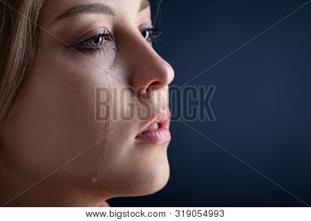 tears on woman face, beauty girl cry on black background
