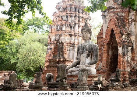 poster of Ruins of Buddha statues and pagoda in Wat Mahathat, the old Thai temple inside Ayutthaya historical park, Thailand