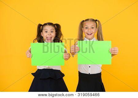School Socialization. Girls School Uniform Hold Poster. Back To School Concept. Schoolgirls Classmat