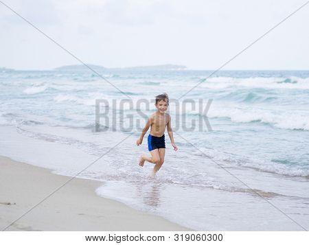 little boy plays on the beach