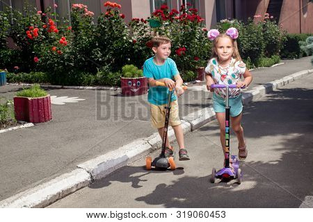 girl and boy ride scooters