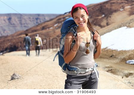 Hiker portrait. Female hiking woman happy and smiling during hike trek on volcano Teide, Tenerife, Canary Islands. Beautiful young mixed race Asian Chinese / Caucasian sporty model joyful.